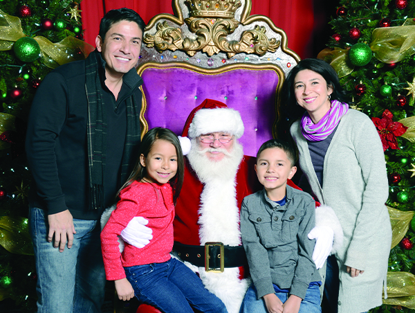 family of 4 pose with Santa Claus
