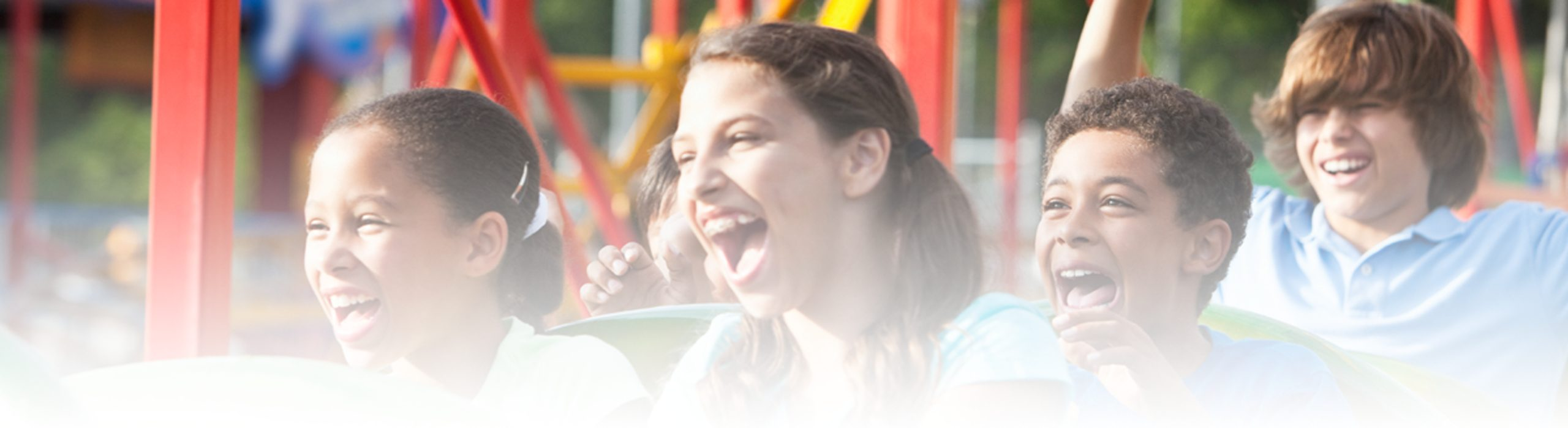 children laughing on rollercoaster